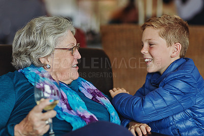Buy stock photo Cropped shot of a senior woman sitting on the sofa with her young grandson