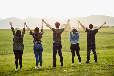 Buy stock photo Rearview of a group of friends standing together on a open field