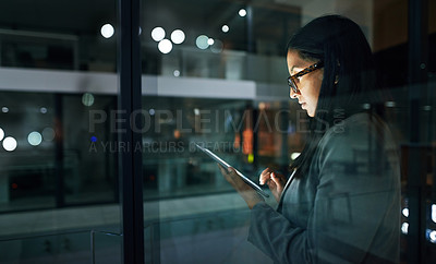 Buy stock photo Shot of a businesswoman using her digital tablet while working late at the office
