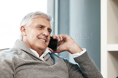 Buy stock photo Cropped shot of a handsome mature man making a phonecall while relaxing on the sofa at home
