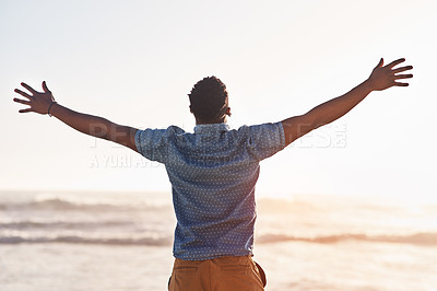 Buy stock photo Rearview shot of a young man standing with his arms wide open at the beach