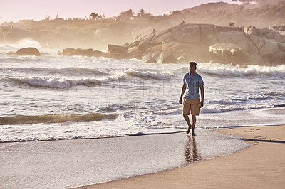 Buy stock photo Shot of a handsome young man going for a walk along the beach