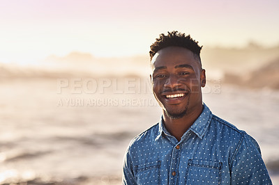 Buy stock photo Portrait of a happy and handsome young man enjoying a day at the beach