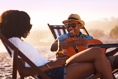 Buy stock photo Shot of a happy young couple relaxing at the beach with drinks and a guitar