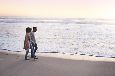 Buy stock photo Shot of a happy young couple going for a romantic walk along the beach at sunset