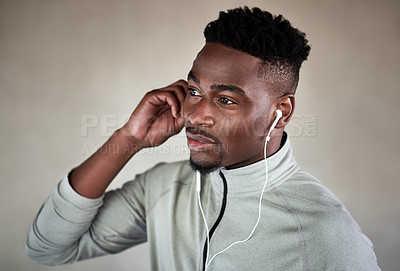 Buy stock photo Cropped shot of a handsome young man listening to music while exercising outdoors in the city