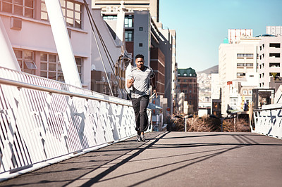 Buy stock photo Full length shot of a handsome young man listening to music while exercising outdoors in the city