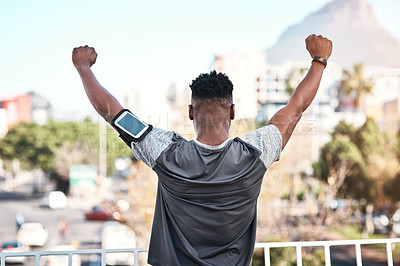 Buy stock photo Rearview shot of an unrecognizable young man standing with his arms raised while exercising outdoors in the city