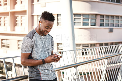 Buy stock photo Cropped shot of a handsome young man checking his text messages while exercising outdoors in the city