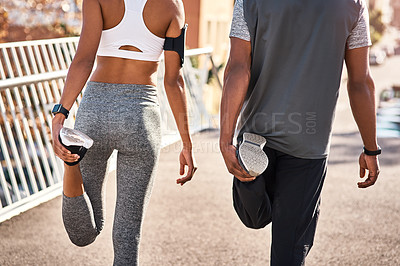 Buy stock photo Rearview shot of an unrecognizable young couple warming up before their workout in the city