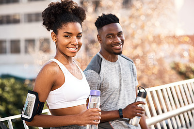 Buy stock photo Cropped portrait of a young couple taking a break for some water while exercising outdoors in the city