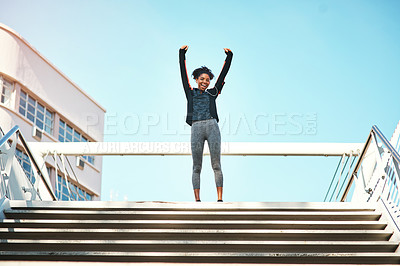 Buy stock photo Full length portrait of an attractive young woman standing with her arms raised while exercising outdoors in the city