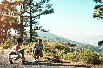 Buy stock photo Full length shot of a young couple fastening their shoelaces before beginning their run