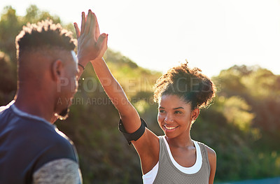 Buy stock photo Cropped shot of a young athletic couple high fiving while exercising outdoors