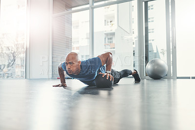 Buy stock photo Shot of a young man working out at the gym