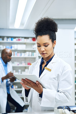 Buy stock photo Shot of a female pharmacist using a digital tablet at work