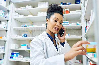 Buy stock photo Shot of a pharmacist talking on her phone while looking at medication