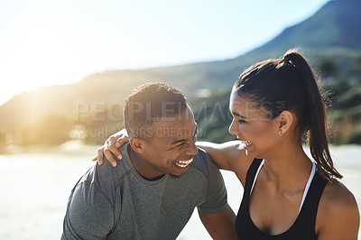 Buy stock photo Shot of a sporty young couple exercising at the beach