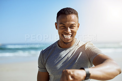 Buy stock photo Portrait of a sporty young man checking his smartwatch while exercising outdoors