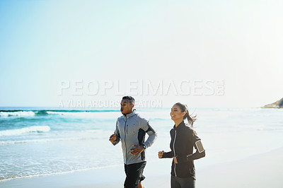 Buy stock photo Shot of a sporty young couple out for a run along the beach