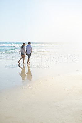 Buy stock photo Shot of a young couple taking a stroll along the beach