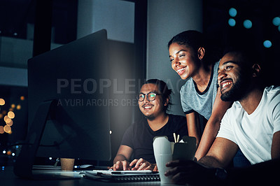 Buy stock photo Shot of a group of businesspeople working together on a computer in an office at night
