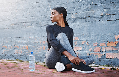 Buy stock photo Shot of a young woman tying her shoelaces before a workout session