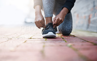 Buy stock photo Cropped shot of a woman tying her shoelaces before a workout session