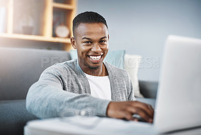 Buy stock photo Portrait of a happy young man using a laptop while relaxing at home