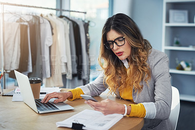 Buy stock photo Shot of a young woman using a mobile phone and laptop in her design studio