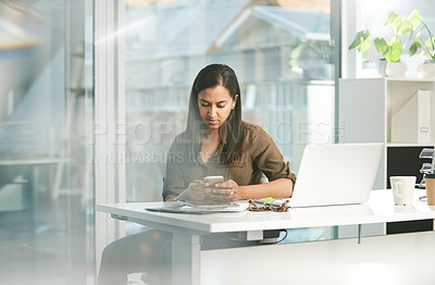 Buy stock photo Shot of a young businesswoman using a cellphone while working in an office