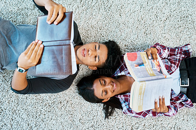 Buy stock photo High angle shot of a young man and woman lying on the floor and reading books at university