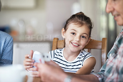 Buy stock photo Shot of an adorable little girl playing cards with her grandparents at home