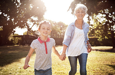 Buy stock photo Shot of an adorable little girl going for a walk with her grandmother in the park