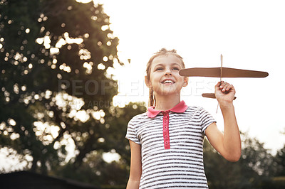 Buy stock photo Shot of an adorable little girl flying a toy airplane outdoors