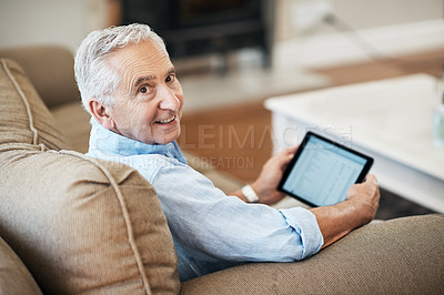 Buy stock photo High angle portrait of a senior man banking on his tablet while sitting on the sofa at home