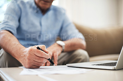 Buy stock photo Cropped shot of an unrecognizable senior man going through his finances while sitting on the sofa at home