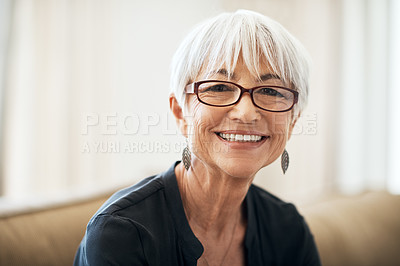 Buy stock photo Cropped portrait of a senior woman sitting on the sofa at home