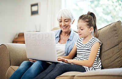 Buy stock photo Shot of an adorable little girl using a laptop with her grandmother at home