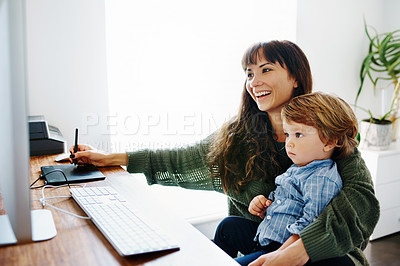 Buy stock photo Cropped shot of a young woman holding her son while doing some work on her computer