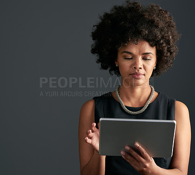 Buy stock photo Studio shot of a young attractive businesswoman using a tablet while posing against a dark background