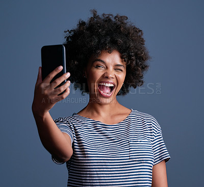 Buy stock photo Studio shot of an attractive young woman taking a selfie on a mobile phone against a blue background
