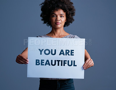 "Buy stock photo Studio shot of an attractive young woman holding a placard with the words ""you are beautiful"" on it"