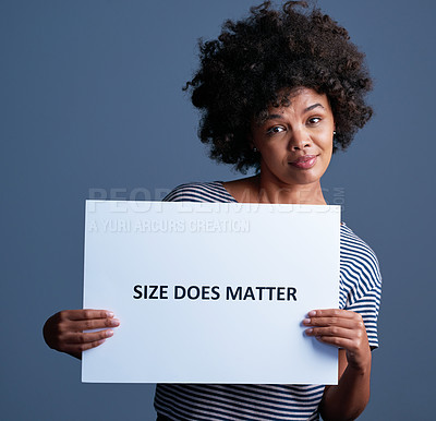 """Buy stock photo Studio shot of an attractive young woman holding a placard with the words """"size does matter"""" on it"""