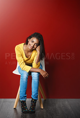 Buy stock photo Studio portrait of a beautiful young woman sitting on a chair against a red background
