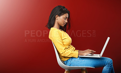 Buy stock photo Studio shot of an attractive young woman using a laptop against a red background