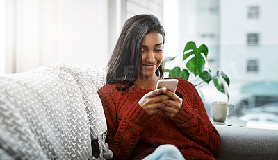 Buy stock photo Cropped shot of a beautiful young woman using a cellphone while chilling on the sofa in the living room at home