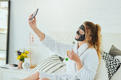 Buy stock photo Cropped shot of an attractive young woman taking selfies while relaxing at home with a glass of tea