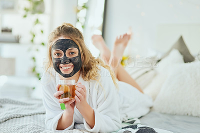 Buy stock photo Cropped portrait of an attractive young woman enjoying a glass of tea while wearing a face mask in her bedroom at home