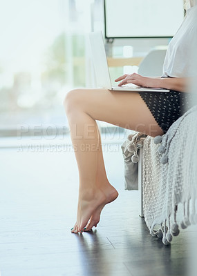 Buy stock photo Cropped shot of an unrecognizable young woman using her laptop while relaxing on her bed at home